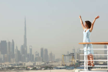 young beauty brunette woman standing on cruise liner deck, putting hands up, city on background
