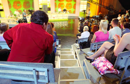 Human backs in auditorium on shooting of television talk-show program