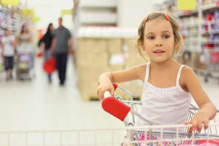 little girl sitting in store cart and looking at side, shelves with commodity photo
