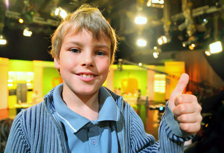 Little smiling boy stands in auditorium and shows ok against the background of television broadcast