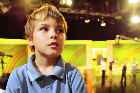 Little boy stands with folded hands in auditorium against the background of television broadcast