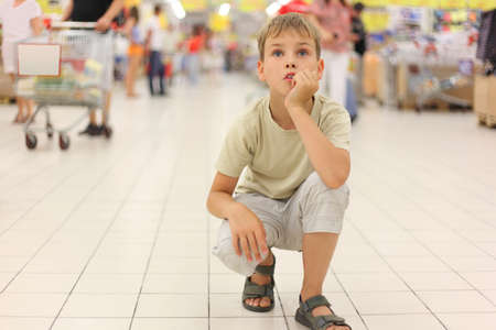 little boy sitting alone on hunkers in big store, chin on hand, looking up photo