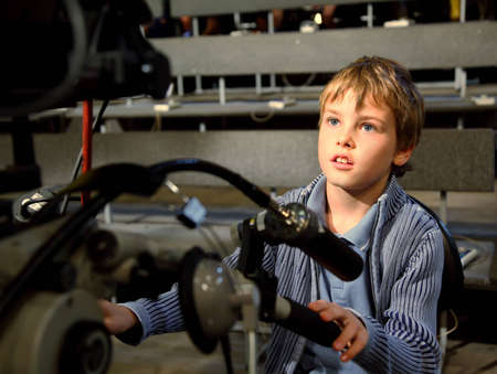 studio picture: Little boy sits on the professional video camera in auditorium on television broadcast