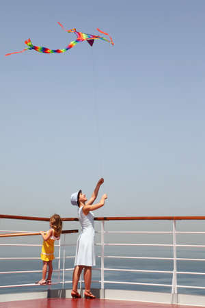 liner transportation: young mother and daughter playing with multicolored kite, standing on cruise liner deck