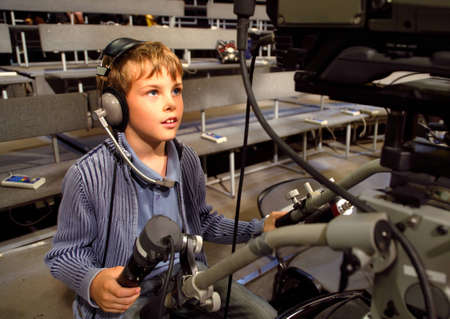 talk show: Little boy with headphones and microphone sits on the professional video camera in auditorium on television broadcast Editorial