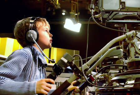 filming: Little boy with headphones and microphone looks to professional video camera in auditorium on television broadcast