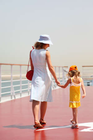liner transportation: young mother and daughter walking on cruise liner deck, sunny day, view from back