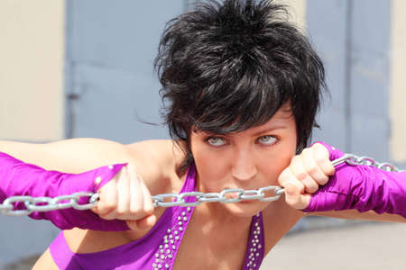 Girl with lush hair and purple clothes serious looks and clinging to chain photo