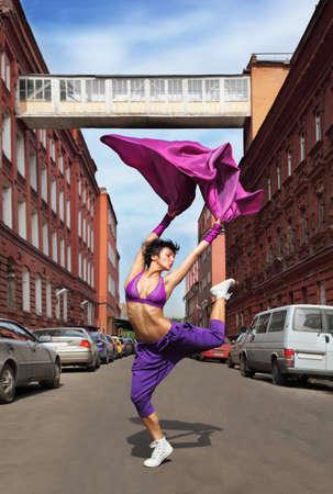 dancer legs: Slim girl in purple clothes dancing with raised leg between buildings Stock Photo