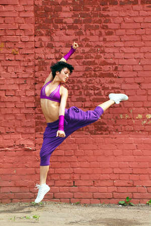 urban dance: Slim girl in purple clothes jumps with raising leg on background of brick wall Stock Photo