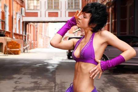 Slim girl in purple clothes posing on background of city street Stock Photo - 12646454