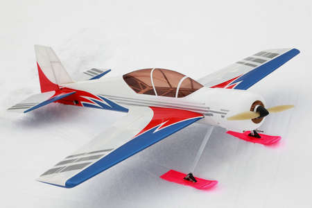 Little model of radio-controlled airplane stands on to snow photo