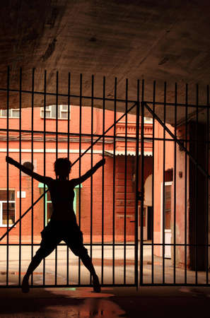 Silhouette of dancing girl in the dark, she open her legs and hands and holding lattice Stock Photo - 12520270