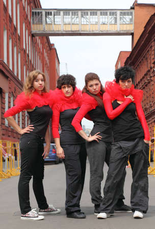 Four girls in same red-black clothes standing on the street between buildings photo