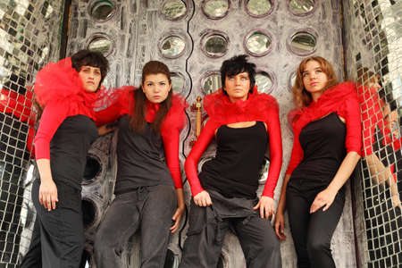 Four girls in same red-black clothes standing on place decorated with mirrors and looking up