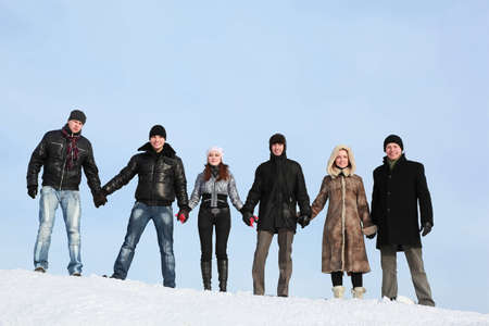 Young people stand on snow and to hold on to hands