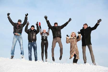 lift hands: Los estudiantes saltar en de invierno en a la nieve y hacia arriba las manos de elevaci�n