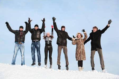 lift hands: Los j�venes saltan en invierno en la nieve y las manos hacia arriba, ascensor Foto de archivo