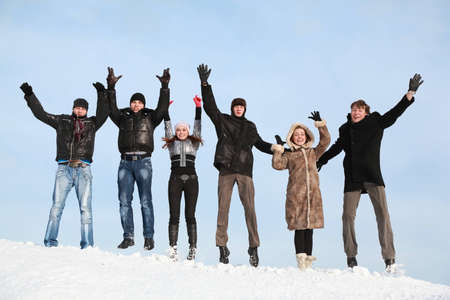 fellows: Young people jump in winter on snow and lift hands upwards Stock Photo