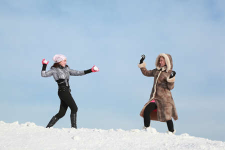 snowballs: Two girls play snowballs and laugh