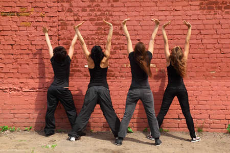 Four girls in same black clothes standing back and raising hands up on background of brick wall Stock Photo