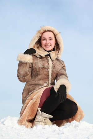 sheepskin: Young woman squatting on  snow and holds  hood  hand Stock Photo