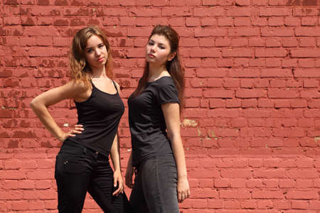 Two serious girls in same black clothes standing on background of brick wall Stock Photo - 12732821