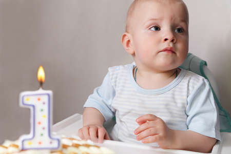first birthday: Little baby celebrating its first birthday, in front of him cake with candle