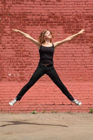 gambe aperte: Ragazza in abiti neri salti con le gambe aperte e le mani sullo sfondo del muro di mattoni