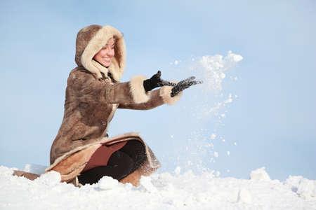 palle di neve: Giovane donna accovacciata e mani gettare la neve