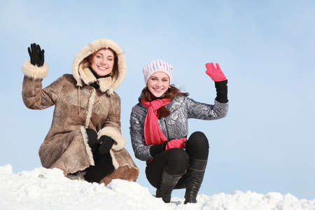 Two girls squatting on snow and waff one-arm Stock Photo - 12732686