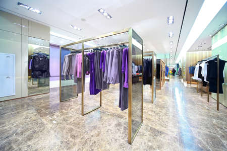 shop interior: Masculine and womanish clothes are for sale in shop, focus on clothes in center