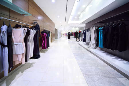 Womanish evening dresses hang on pegs in shop