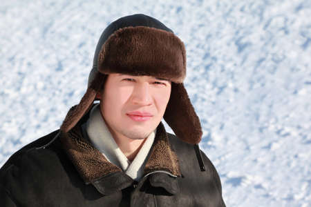 Young man stands in ear-flaps hat in winter and concentrated looks ahead Stock Photo - 12732765