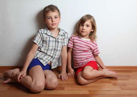 piedi nudi ragazzo: Piccolo ragazzo sorridente e una ragazza pensosa in casa abiti da seduto e appoggiato contro il muro Archivio Fotografico
