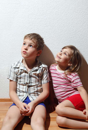 looking in corner: Little smiling girl and thoughtful boy in home clothes sitting and looking to up corner