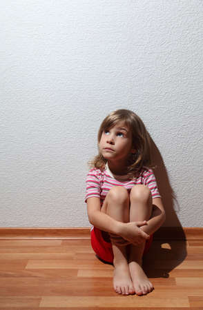 Little girl in casual clothes looks sad to corner, whence comes the light 스톡 콘텐츠