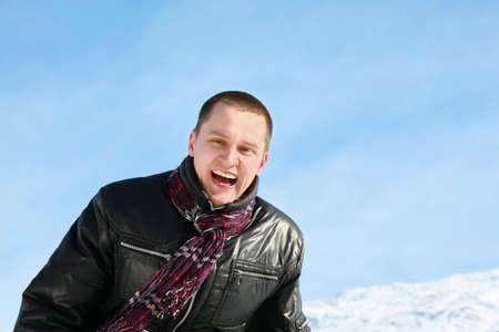 Young man laughs merrily in day-time in street in winter Stock Photo - 12732621