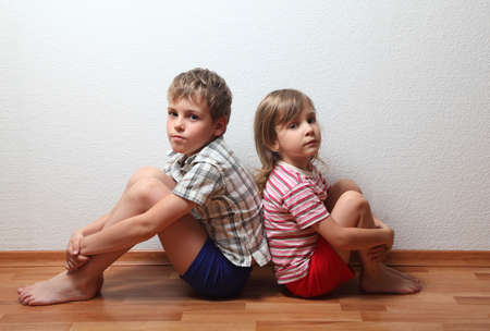 Thoughtful boy and girl in home clothes sitting back to back Stock Photo - 12647340