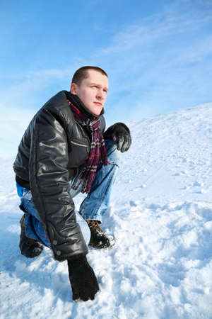 leans on hand: Man concentrated looks  winter of squatting  in sky and leans  hand on snow