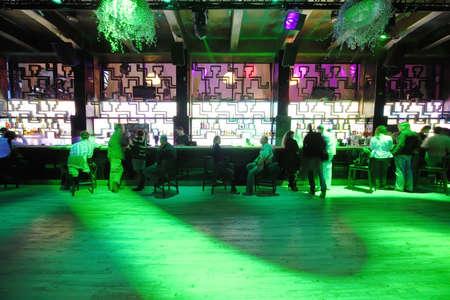 night club: MOSCA, RUSSIA - 28 agosto: Long pista da ballo vuota nei pressi di bar con la gente in luci verdi di night-club il 28 agosto 2010 a Mosca, Russia. In Russia ha registrato 1,5 mila night club per il 2010.