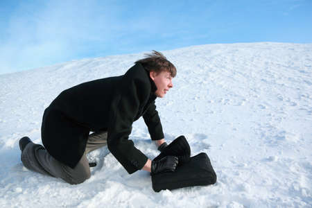 all seasons: Young man creeps on all fours on snow with  brief-case Stock Photo