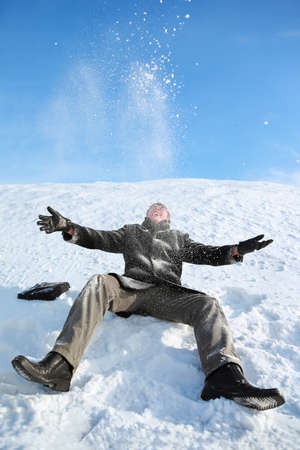 Young man sitting on snow and throw him upwards  and makes merry Stock Photo - 12732786