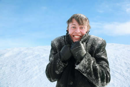 froze: Young man froze and hides  head in collar of winter overcoat