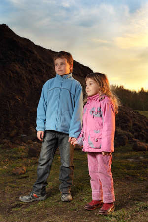 Little girl in pink clothes and boy in blue jacket standing near hill at evening photo