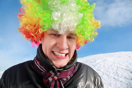 Fellow in wig of clown stands by winter day and smiles Stock Photo - 12732966