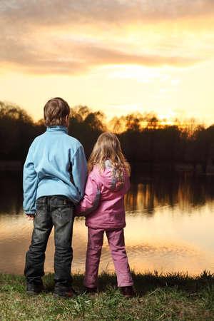 bewonderen: Klein meisje in roze kleding en jongen in blauwe jas staan terug op de oever van de rivier en bewonder op zonsondergang
