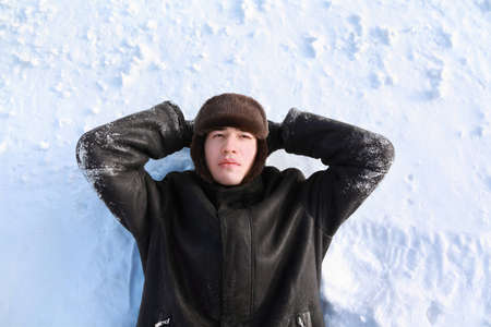 Young man lies on back on snow locate hands for head and looks dreamily Stock Photo - 12732768