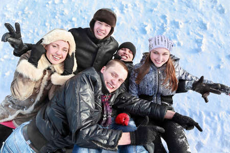 Students welter together in  heap on  snow photo