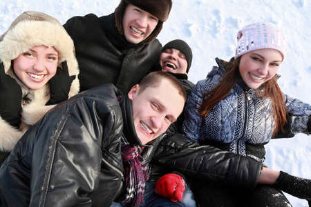 Young people by winter day lie on snow in heap and laugh photo
